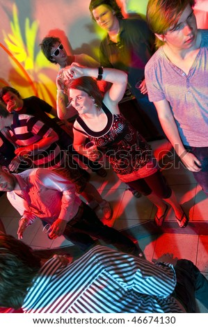 Dancing people in a nightclub with various light effects and motion - stock photo