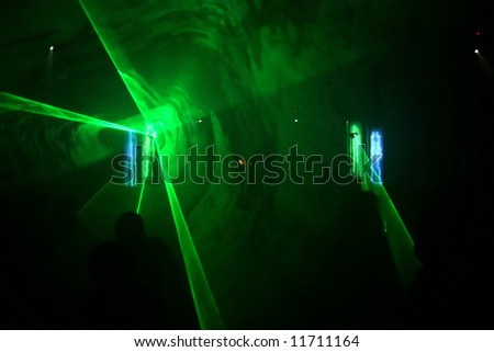 Dancing people in front of green laser lights