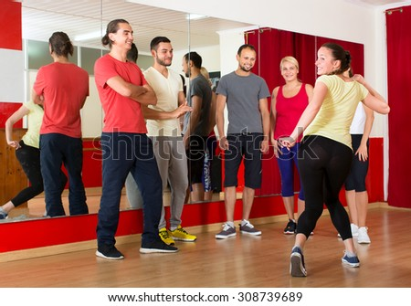 Dancing teacher showing new moves to group of students at a dancing lessons in a gym - stock photo