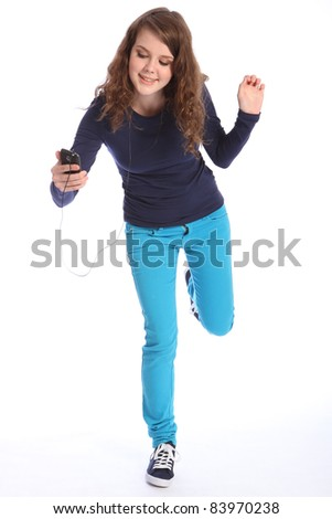 Dancing to music on her phone a beautiful teenager girl with bright blue eyes has fun in studio wearing blue jeans and navy long sleeved top and blue trainers. She has long brown hair.