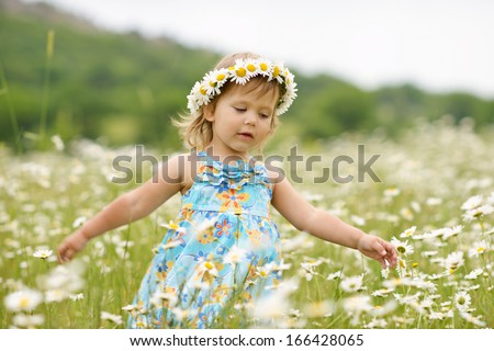 dancing toddler girl in the daisy field