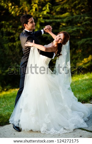 dancing wedding couple at a park on a sunny day - stock photo
