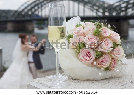 dancing wedding couple - focus on glasses and bouquet in foreground - stock photo