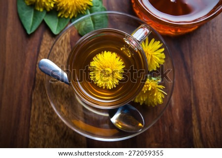 dandelion tisane tea with fresh yellow blossom inside tea cup, on wooden table - stock photo
