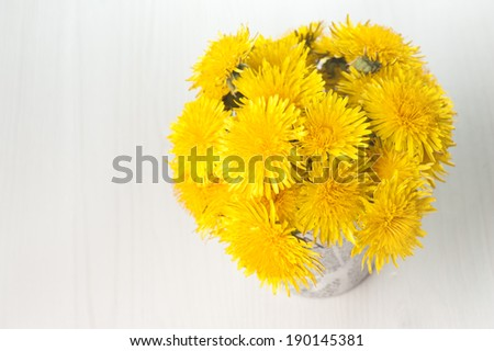 Dandelions in a basket on white wooden background  - stock photo