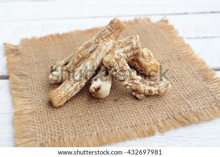 dang gui (angelica sinensis, dang gui ginseng) on wooden background, traditional chinese herbal medicine. - stock photo