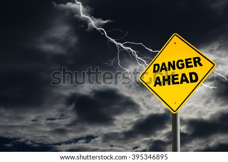 Danger Ahead road sign against a dark, cloudy and thunderous sky. Conceptually warning of danger ahead. - stock photo