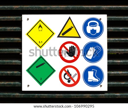 Danger and safety symbols on rusty door to gas storage. - stock photo