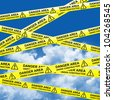 Danger Area and Under Construction Caution Tape With Blue Sky Background - stock photo