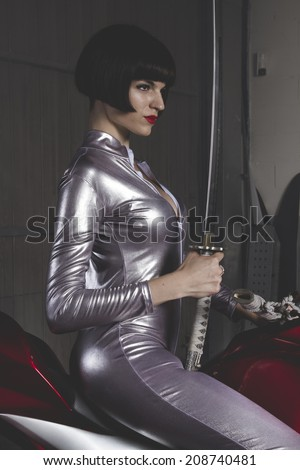 Danger, Beautiful brunette woman wearing latex mounted on a motorcycle with a modern design - stock photo