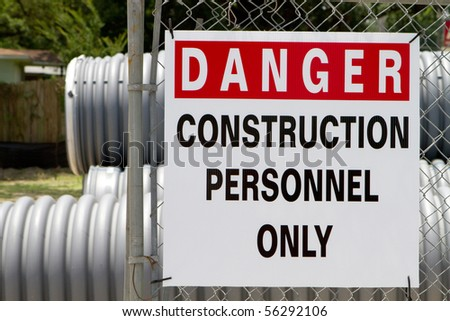 Danger Construction Personnel Only sign hangs on a chain link fence outside a construction site. - stock photo