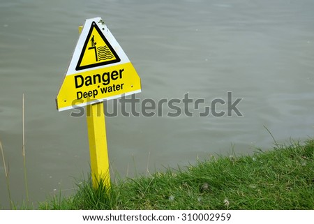 Danger deep water sign on golf course pond.