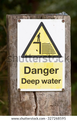 Danger Deep Water sign on wooden post besides river - stock photo