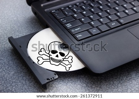 Danger DVD or CD in tray of computer laptop - stock photo
