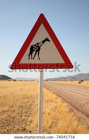 Danger Giraffe Crossing Road Sign close to Country Road, Namibia, South West Africa - stock photo