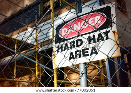 Danger hard hat area safety warning sign on a chain link fence at a house construction work site - stock photo