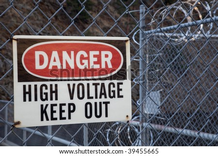 danger, high voltage, keep out -  warning sign on a chain link fence with barbed wire on top protecting hydro power plant - stock photo