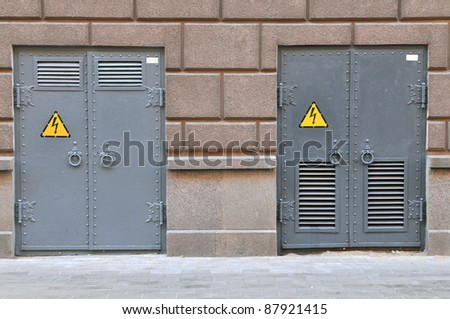danger high voltage sign on a two rusty metal door - stock photo