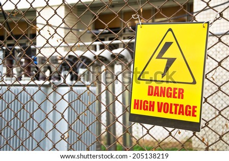 Danger high voltage warning sign on a fence in transformer station. - stock photo