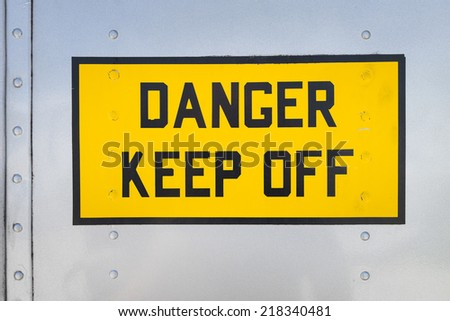 Danger Keep Off, yellow warning sign on the fuselage of a helicopter, USA - stock photo