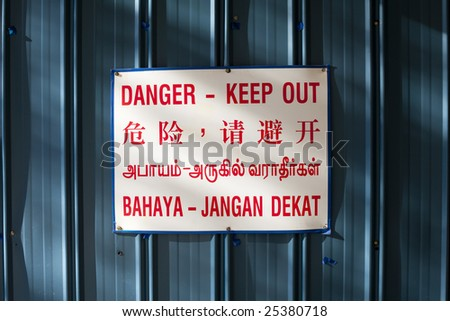 Danger keep out warning sign against blue metal in four languages: English, Chinese, Tamil and Malay