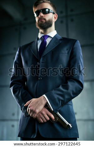 Danger man agent with gun and sunglasses. Focus on hands and gun. - stock photo
