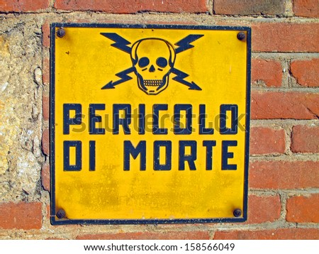 Danger of death signs with skull and crossbones written in Italian and brick wall - stock photo