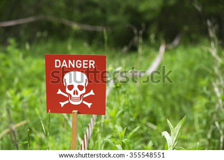 Danger of mines or poison sign on a field - stock photo