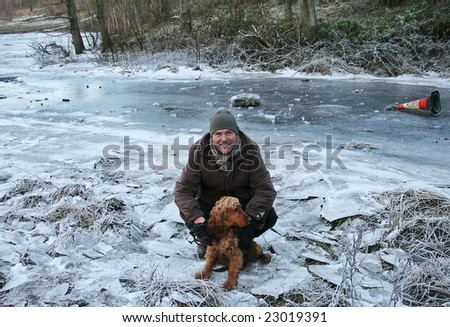 Danger on thin Ice, smiling Man surrounded by broken Ice holds Spaniel who was playing on frozen River. Not the place to park as you can see by the Car Tyre and Parking cone in the background - stock photo
