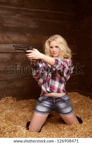 Danger sexy woman with revolver over pile of straw texture background