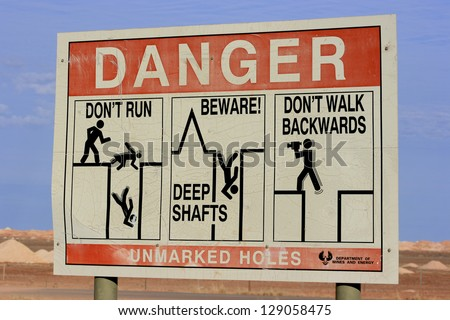 Danger Sign at Coober Pedy, South Australia, Australia warning not to fall into old opal mine shafts. - stock photo