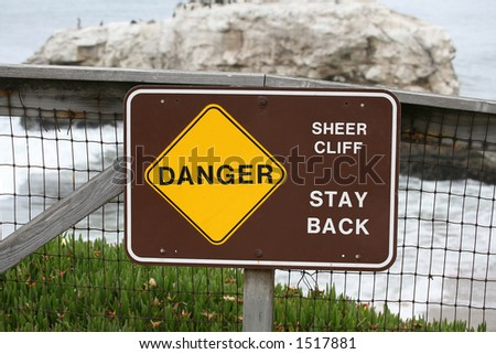 Danger sign at the cliff's edge - stock photo
