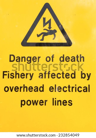 Danger sign for fishermen to be careful with fishing rods near electric power lines. - stock photo
