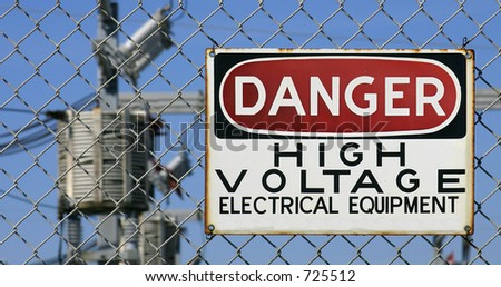 Danger Sign hanging on a fence. White, black and red sign warning of electrical hazard - stock photo