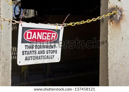 Danger sign is zip tie to a metal chain. - stock photo