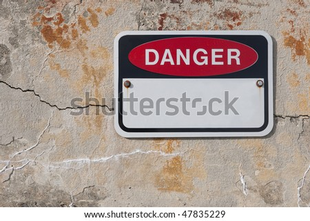 Danger sign on cool rough old stone weathered wall