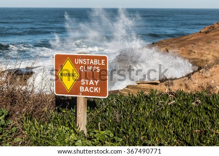 Danger sign with crashing waves and ocean spray in background at Sunset Cliffs in San Diego, California.  - stock photo