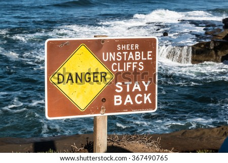 Danger sign with ocean background at Sunset Cliffs in San Diego, California - stock photo