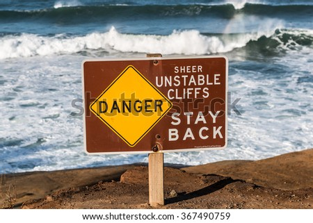 Danger sign with waves in background at Sunset Cliffs in San Diego, California.  - stock photo