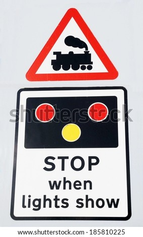 Danger, stop when lights show, a railway crossing roadsign with an illustration of a steam locomotive, against a grey background.  - stock photo