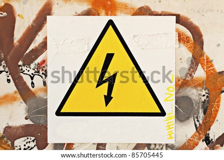 Danger symbol over a white cartel, over a wall with graffitti - stock photo