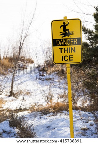 Danger thin ice sign, photographed on the edge of a snow and ice covered lake, with sparse grass emerging through the snow. - stock photo