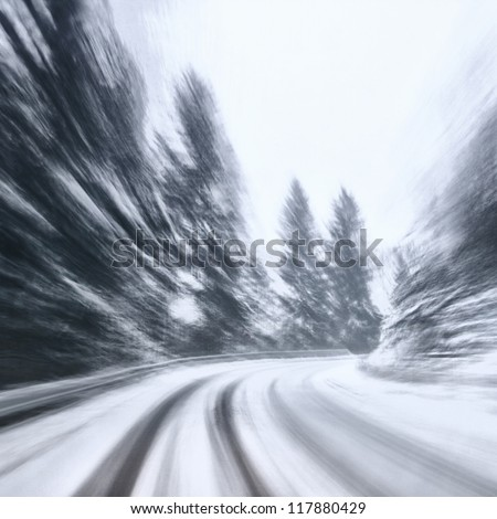 Danger turn at the heavy snow road. Motion blur visualizies the speed and dynamics. - stock photo
