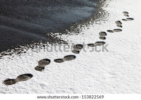 Danger walking in the snow on the asphalt. - stock photo
