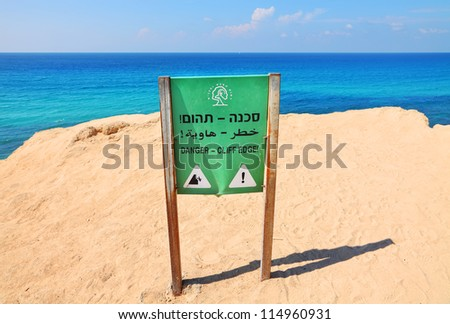 Danger Warning sign on the high cliff of the Mediterranean Sea coast - stock photo