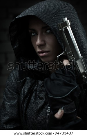 Danger woman with gun. Dark colors. - stock photo