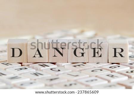 danger word background on wood blocks - stock photo