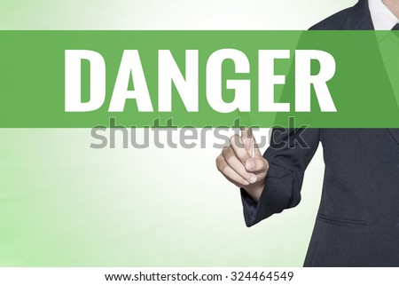 Danger word on green virtual screen touching by business woman - stock photo
