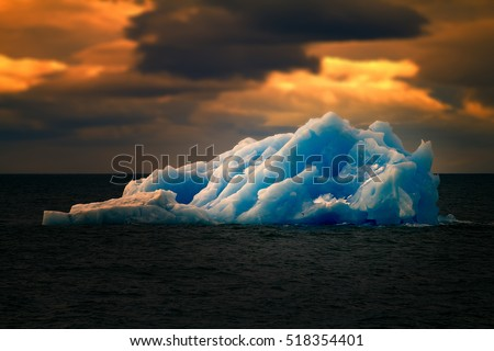 Dangerous and alluring Arctic. Terrible and magnificent iceberg in polar ocean of blue ice, similar to one that sunk Titanic.