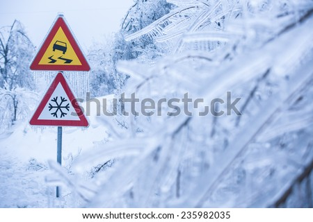 Dangerous and icy road with sleet covered trees - stock photo